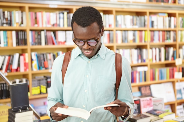Красивый молодой афроамериканский хипстер в оттенках, держащий открытую книгу в его руках, читая его любимое стихотворение, ища вдохновение в публичной библиотеке или книжном магазине. люди, образ жизни и досуг