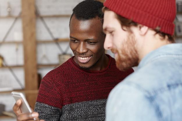 現代のテクノロジー、人々、レジャー、オンラインコミュニケーション。携帯電話を持って、画面を見て、笑顔のスタイリッシュな白人の友人に何かを見せて幸せな若い浅黒い男性