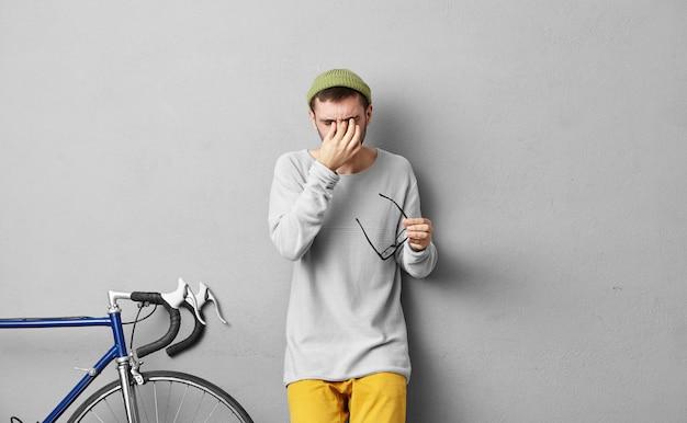 人と疲労の概念。おしゃれな服を着て、眼鏡を脱いで目を掻き、一人で自転車で長い旅の後に疲れている、厚いひげを持つ若い魅力的な男性
