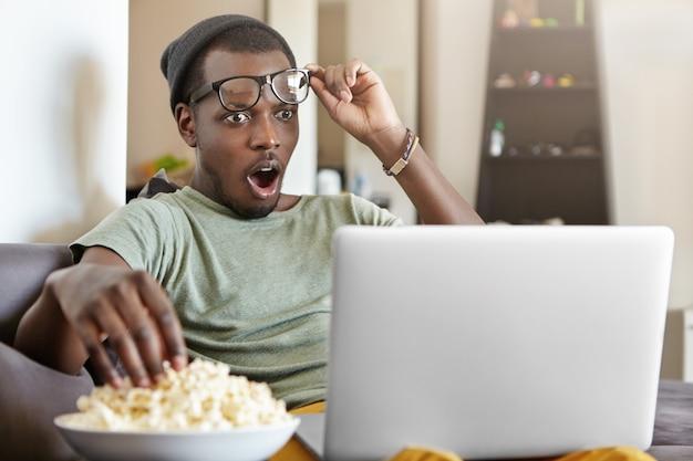 現代のライフスタイル、技術、人々の概念。驚いた若いアフリカ系アメリカ人男性は、仕事の後に自宅でリラックスしてバスケットボールの試合をオンラインで見たり、ソーシャルメディアのビデオを見たり、ポップコーンを食べたりしています