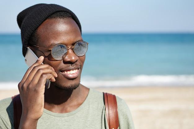 丸い色合いと帽子を身に着けているハンサムな幸せなアフロアメリカンの学生が両親に携帯電話で話し、夏休み中に一人で旅行しているときに大丈夫だと言っている