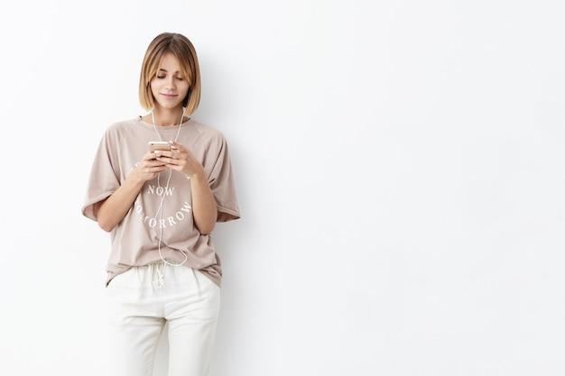 Молодая кавказская женщина с короткой прической, небрежно одета, держит в руках сотовый телефон, печатает сообщения, слушает музыку в наушниках