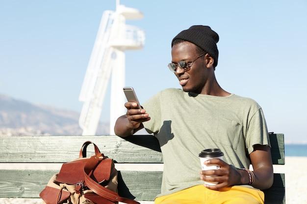 Открытый портрет модного улыбающегося афроамериканского мужского туриста, наслаждающегося кофе из бумажного стаканчика и ищущего новые интересные места на сайтах с помощью онлайн-приложения на мобильном телефоне