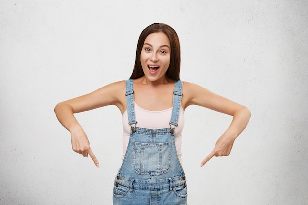 Портрет молодой привлекательной женщины брюнетки, носящей белый комбинезон футболки и джинсовой ткани, указывающий с пальцами передней части вниз, имея счастливое выражение, рекламируя что-то. женщина показывая что-то