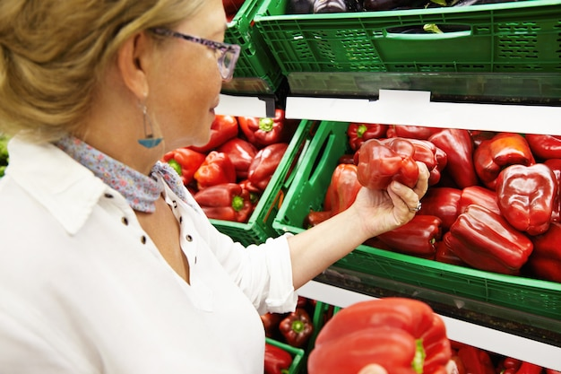 魅力的な女性の年金受給者が食料品店やスーパーの農産物売り場で果物や野菜を買い、家族の夕食に大きな赤唐辛子を拾い、最高のものを選びます。