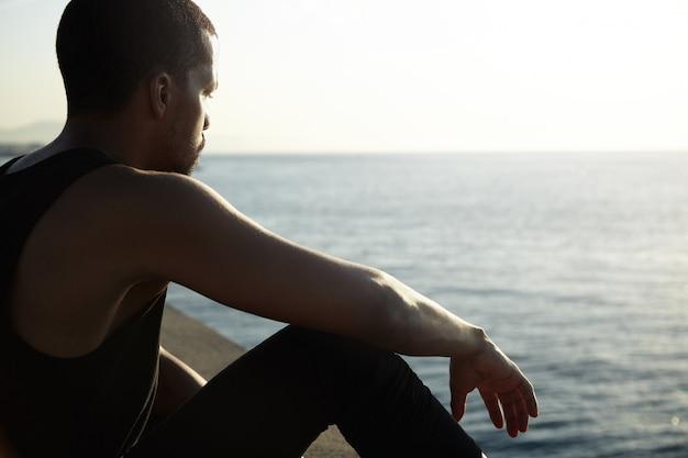 穏やかな海の素晴らしい風景を考えている若いアフリカ人