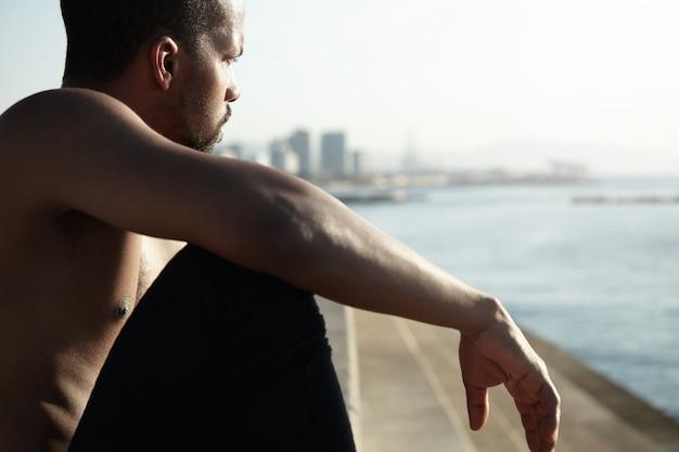 伸ばした腕を膝に乗せて川岸の散歩に座っている若いバガボンド。黒肌の男は大都市での生活を考え、水の波を見て、日光の下でリラックスしています。