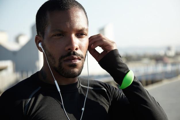 ひげが彼の耳にヘッドフォンを入れて若い黒人男性のクローズアップショット。断固としたスポーツマンが日の出で長距離のランニングとトレーニングの準備ができています。スポーツフィットネストラッカーを身に着けている運動選手。