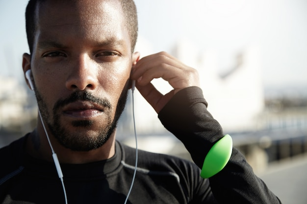 タフなトレーニングのために自分自身を準備する目的のフィットネストレーナーの肖像画。真面目な顔、トラッカー、耳の中にあるヘッドフォンで、アフリカ系アメリカ人のアスリートはスポーツに挑戦する決意です。
