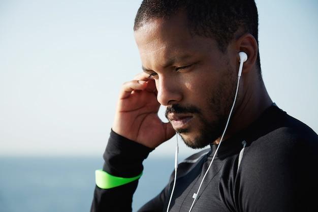 人間と技術の概念。彼の携帯電話で音楽を聴くためにイヤホンを使用してハンサムなアフリカ系アメリカ人男性