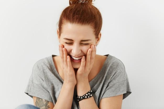 Модная красотка с узелком для волос и татуировкой, одетая в стильную серую футболку, держащая руки за щеки и закрывающая глаза