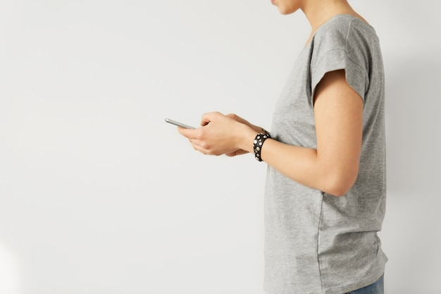 人、現代のテクノロジー、ガジェット。ソーシャルメディア中毒。スマートフォンで入力してインターネットをサーフィンするスタイリッシュな白人女性のトリミングされた側面図