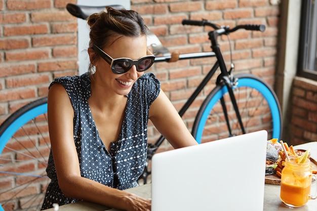 テクノロジーとレジャーのコンセプト。モダンなコーヒーショップで昼食をとりながら友人にビデオ通話をかけるスタイリッシュなサングラスを着て魅力的な女性