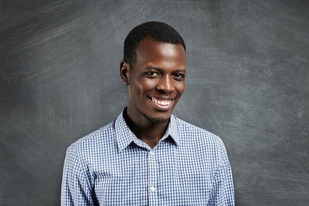 陽気な笑顔で探している空の黒板に立っている市松模様のシャツに身を包んだ小さなひげを持つ幸せな浅黒い肌の男。人間の顔の表情、感情、感情