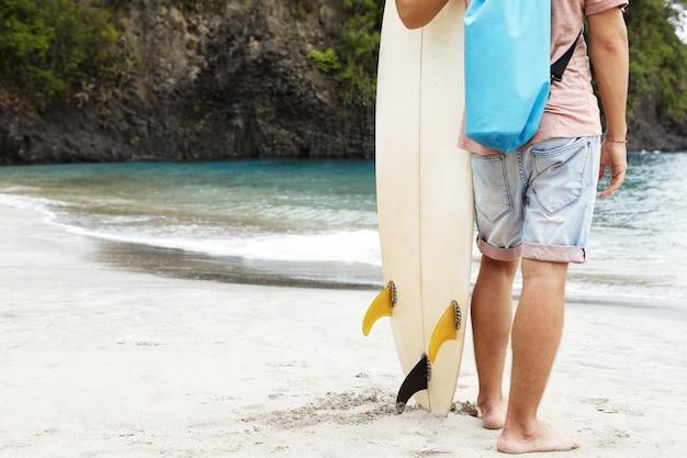 波が当たる準備ができている彼の白いサーフボードを運ぶ、植生のある高い岩の多い海岸に対して砂浜に立っている裸足の若いサーファーのトリミングされた肖像画