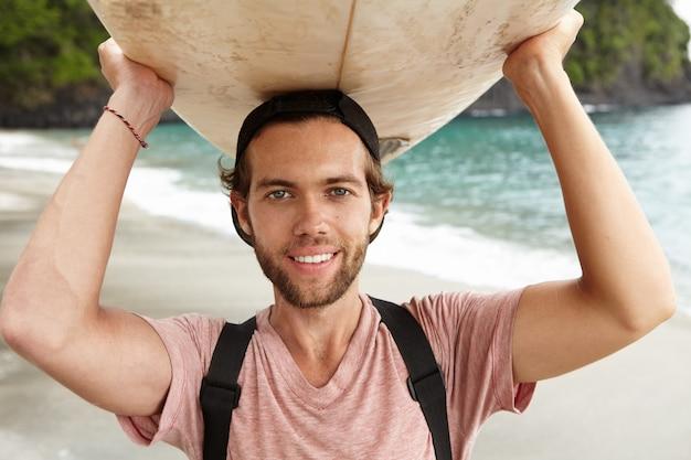エクストリームスポーツと健康的なライフスタイルのコンセプト。海に行く途中で彼の頭にサーフボードを運ぶ幸せな笑顔若いひげを生やしたサーファーのクローズアップ表示