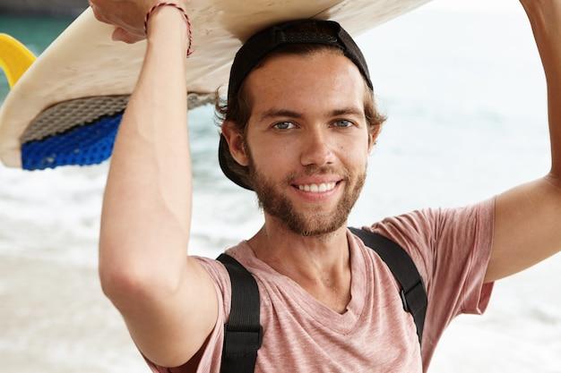 人、趣味、レジャーのコンセプト。幸せな若いひげを生やしたサーファー彼の頭の上にサーフボードを押し、元気に笑顔
