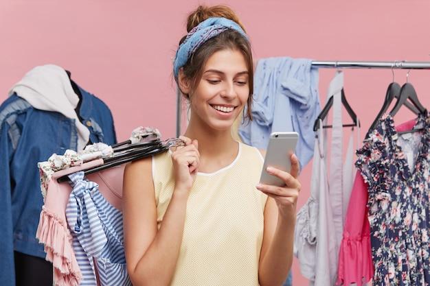 Счастливая женщина стоя на магазине одежды, обмениваясь сообщениями с другом над умным телефоном пока пробующ новые одежды прося совет что купить. жизнерадостная женщина, используя современный мобильный телефон в торговом центре.
