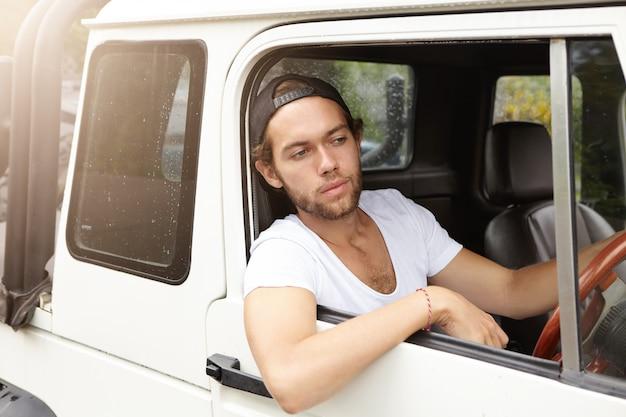 人、レジャー、旅行、休暇の概念。交通渋滞を回避しようとしながら彼の白いクロスオーバーユーティリティ車を運転するスナップバックを着ておしゃれなひげを剃っていない男
