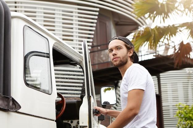 彼の白い四輪駆動車のドアを開けてスナップバックを着て、笑顔で目をそらしているファッショナブルな若い白人男性学生
