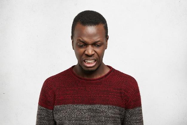 Сердитый привередливый молодой темнокожий мужчина в свитере из джерси смотрит вниз, с брезгливым пренебрежительным взглядом позирует в помещении у серой стены