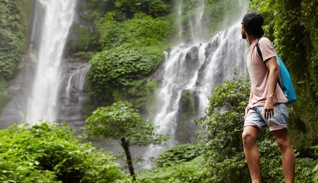 自然を楽しむデニムショートパンツとスナップバックの若いハイカーまたは冒険家の全身像