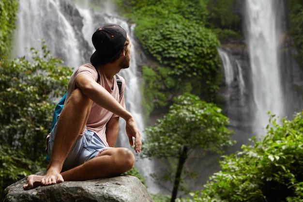自然、野生動物、旅行のコンセプト。大きな石の上に座って彼の周りの美しい景色を楽しんでいるスナップバックを身に着けている裸足の若いハイカー。熱帯雨林の奥深くでリラックスしたヒップスター