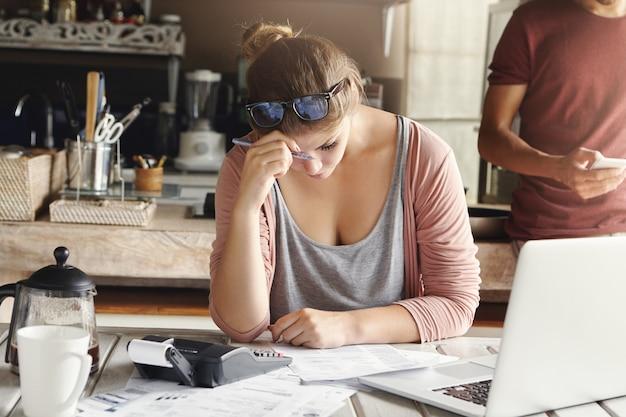 信用問題に直面している落ち込んでいるカップル。自宅でアカウントを作成し、家計を削減するために一生懸命努力し、ペンを持って電卓で必要な計算をしている間、疲れているように見える妻を強調しました
