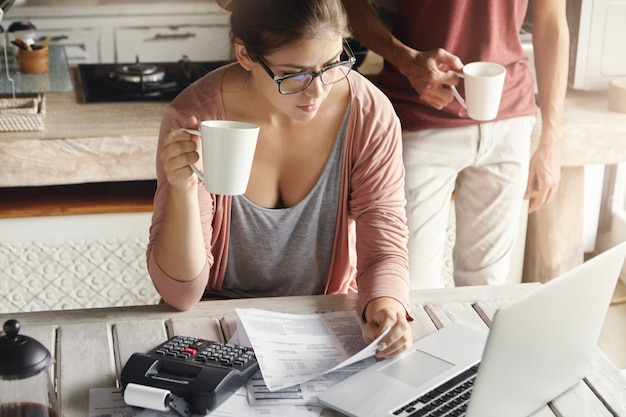 若いカップルが自宅で家族の費用を計算します。公共料金をオンラインで支払う眼鏡の女性、コーヒーやお茶を飲んでいる、ドキュメントと計算機を備えたキッチンに座っている、ノートパソコンの画面を見て