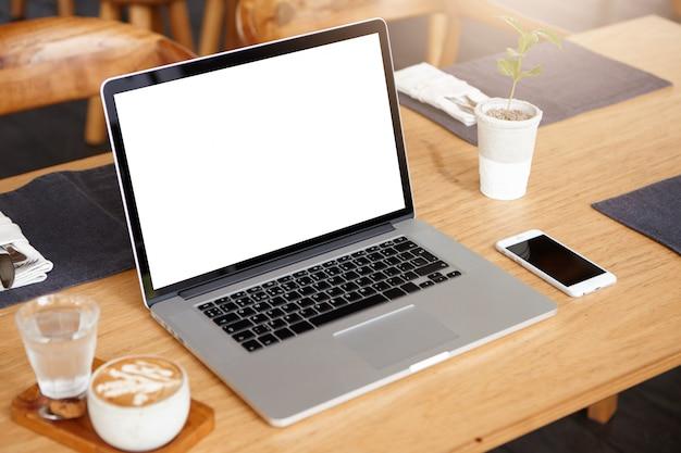 ビジネス、技術、コミュニケーションの概念。白い空白の画面を持つ現代のラップトップコンピューターでミニマルなワークスペース