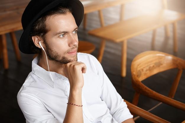 黒い帽子とイヤホンを空想に身に着け、ファッショナブルな幸せな若い男が彼のお気に入りのバンドの新しい音楽アルバムをオンラインで楽しんで、カフェで一人でリラックスしながら電子機器で無料のアプリケーションを使用している