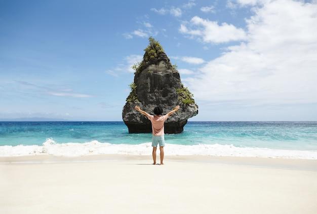 砂浜の海岸線に裸足で立って、海の真ん中にある岩の崖に面し、彼の周りのすべてのこの美しさを抱こうとするかのように彼の腕を大きく開いたままにする若いヒップスターの背面図