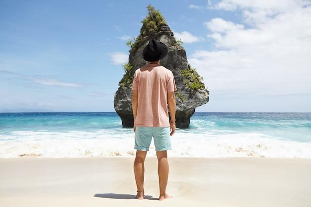 砂浜の海岸、岩だらけの島、そして彼の前を走る広大なターコイズブルーの海で裸足でポーズをとるトレンディな黒い帽子をかぶったファッショナブルな男性モデルのリアショット。人、観光、旅行、冒険