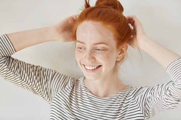人とライフスタイルのコンセプト。生姜髪とそばかすのある肌を着て魅力的な若い女性は彼女の友達とパーティーに行く前に彼女の髪型を調整しながら幸せそうに笑ってストライプトップを着ています。