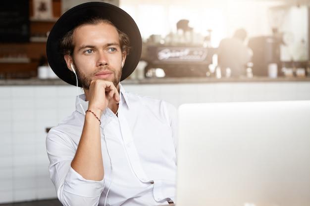 Привлекательный молодой человек держит руку на подбородке, задумчиво смотрит, сидит перед открытым ноутбуком в наушниках и слушает аудиокнигу онлайн