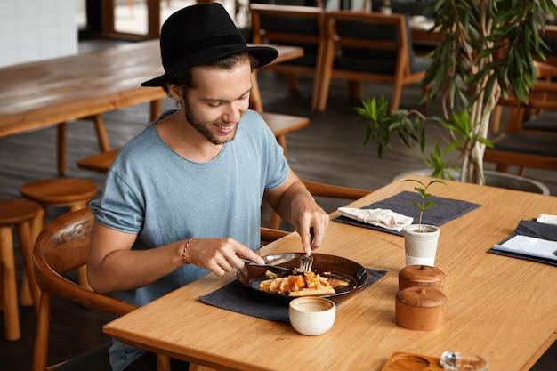 Съемка в помещении счастливого молодого студента в стильной шляпе, едящей вкусную еду с ножом и вилкой во время перерыва в столовой университета, наслаждаясь свежим и здоровым обедом