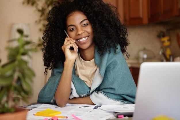 人、現代の技術とコミュニケーションの概念。一般的なラップトップとテーブルの上のペーパーで居心地の良いキッチンインテリアに座って、電話での会話を持つ美しい浅黒い女性の屋内でのショット