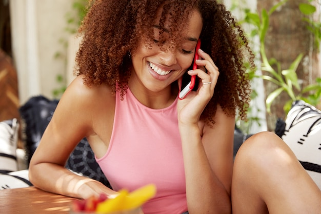 人、民族、およびコミュニケーションの概念。ダークスキンの若いかわいいアフリカ系アメリカ人女性は、ボーイフレンドや恋人との電話での会話を楽しんでおり、一人で居心地の良い国内のインテリアに対して座っています。