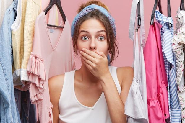 口を手で覆い、虫眼鏡の目で見て、彼女の衣装にアイロンをかけるのを忘れて、ビジネス会議に向けてショックを受けたショックを受けた女性モデルの肖像画。人、ショック、驚き