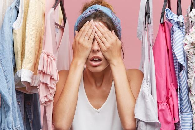 Молодая привлекательная женщина закрыла глаза руками, ожидая удивления от своего парня, который купил ей новое платье. красивая женская модель, ожидающая чего-то, стоя в гардеробе