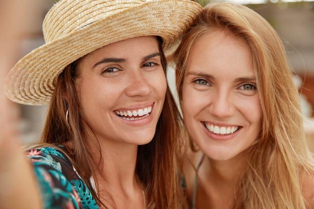 愛らしい女性のクローズアップショットには、友好的な関係があり、自撮りをし、幅広い笑顔を持ち、互いに近くに立っています。同性愛者のカップルがトロピカルリゾートで一緒に再現します。ポジティブネスのコンセプト