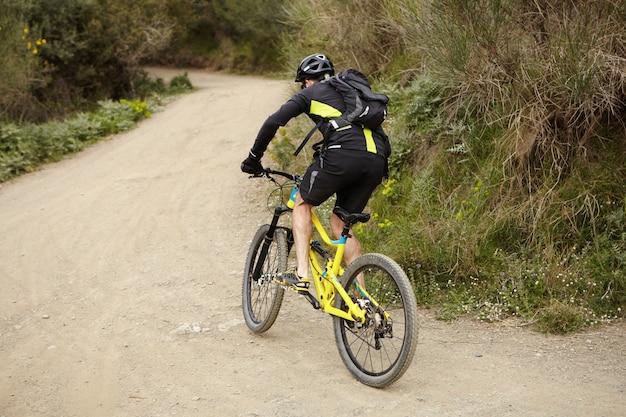 人、スポーツ、極端なリスク、アクティブな健康的なライフスタイルのコンセプト。森の道に沿って高速の黄色のマウンテンバイクに乗ってサイクリング服と防護服を着ている若いヨーロッパの男性サイクリスト