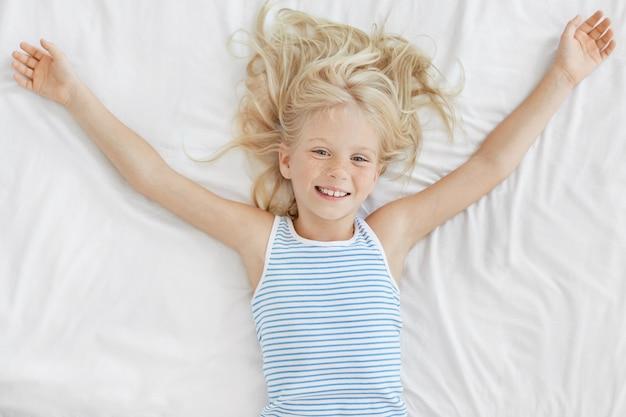 Жизнерадостная девочка со светлыми волосами, лежа в удобной кровати на белом постельном белье, растягиваясь после ночного сна, смотрит с восхитительным выражением лица. веснушчатый маленький ребенок отдыхает в постели
