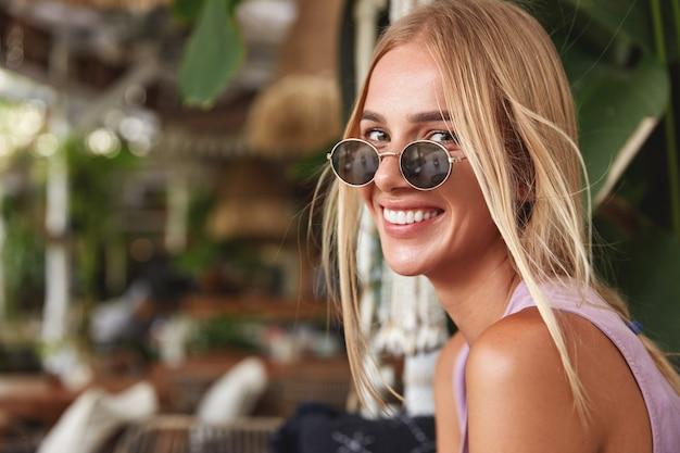 幸せな金髪の女性はトレンディなサングラスをかけ、白い完璧な歯を見せ、嬉しそうに笑い、レクリエーションの時間を楽しんでいます。人、美容、感情、残りのコンセプト