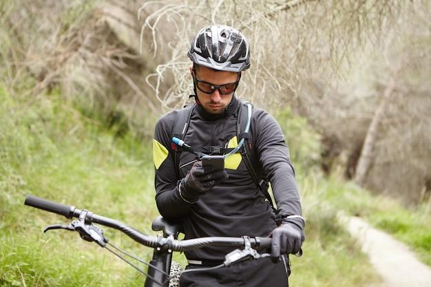 人、アクティブなライフスタイル、スポーツ、テクノロジーのコンセプト。屋外のモーター付き自転車でサイクリングしながら小さな休憩中に携帯電話でインターネットを使用して防護服を着ている深刻な男性ライダー
