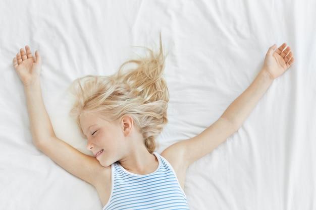 Симпатичная белокурая маленькая девочка в матросской футболке спит на удобной кровати на белом постельном белье, улыбаясь во время приятных снов. маленькая девочка чувствует себя усталым в постели после долгих игр