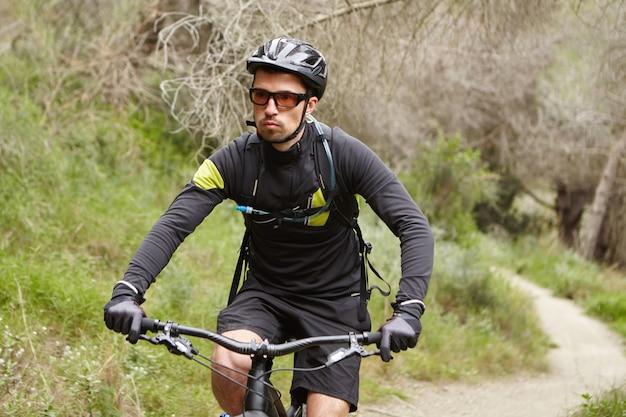 Серьезный красивый мужчина-байкер в черной спортивной одежде, шлеме и очках несется на мотоцикле с педальным двигателем по тропе в лесу, имея уверенный и самоопределенный вид