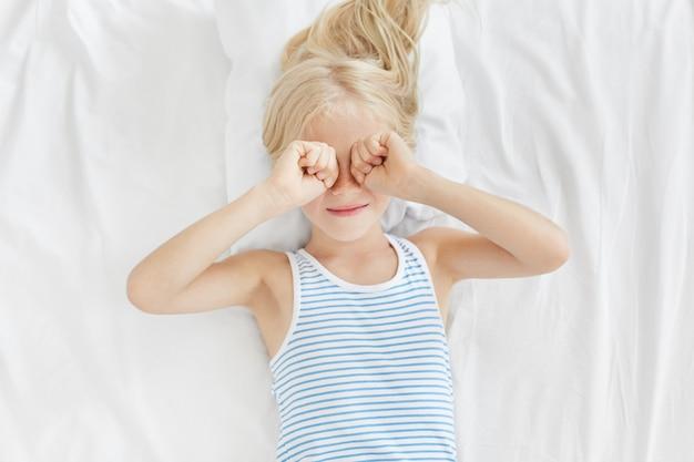 Внутренний снимок маленькой девочки, потирающей глаза утром после пробуждения, лежащей на белом покрывале, желающей больше спать. сонный ребенок, лежа на кровати, с усталым выражением лица, когда хочет спать