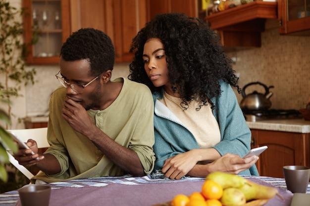 関係、秘密、嫉妬、不貞の概念。彼の裏切りの疑いのある不思議な嫉妬深い美しい若い黒肌の女性は彼のボーイフレンドの肩越しに好奇心が強い表情で見ています