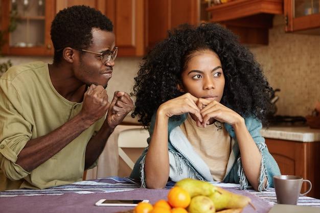 無関心な妻に怒り狂った拳で腹を立てる怒りに満ちた黒。台所のテーブルで深刻な喧嘩を持っているアフリカのカップル